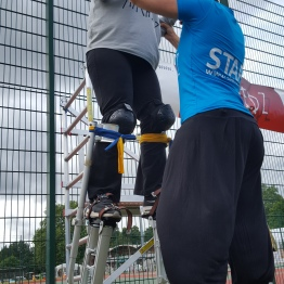 Sarah helps a woman on stilts.