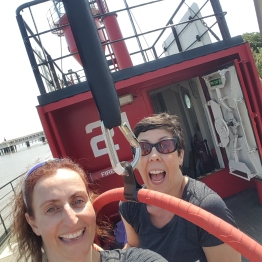 Tina & Sarah smile to the camera, close to aerial hoop, suspended on a boat.