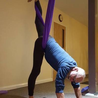 Man extends into vertical splits, hands on ground, in aerial yoga pose.