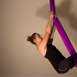 Tina hovers in the air in aerial yoga pose.