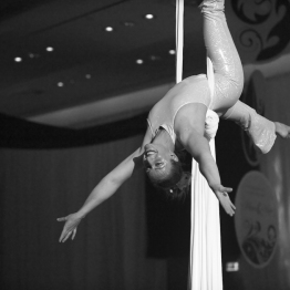 Tina hangs upside down, smiling on aerial fabric.