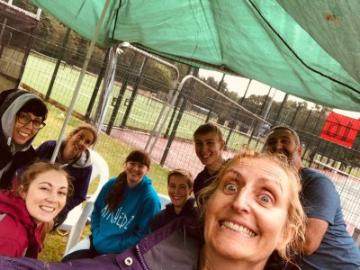 The Airhedz team smile out at the camera. All are huddled under a makeshift canvas cover, hiding from the rain.
