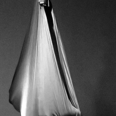 Body tightly cocooned in an aerial hammock