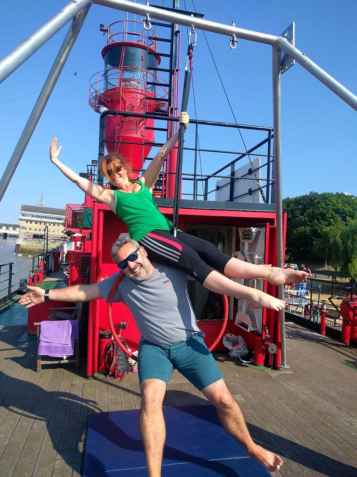 Steve and Shari share an aerial hoop. Both extend an arm and grin towards the camera.