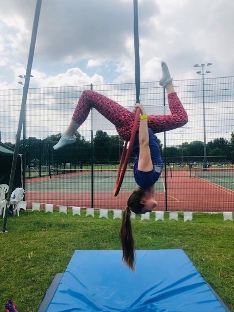 Jessica hangs from the top of an aerial hoop, legs apart in splits.