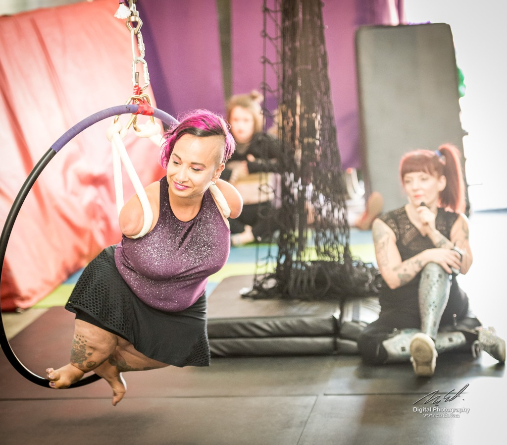 A short-statured woman with should-length arms and no hands suspends from two hand-loops on an aerial hoop. Amputee Erin Ball is in the background holding a microphone.