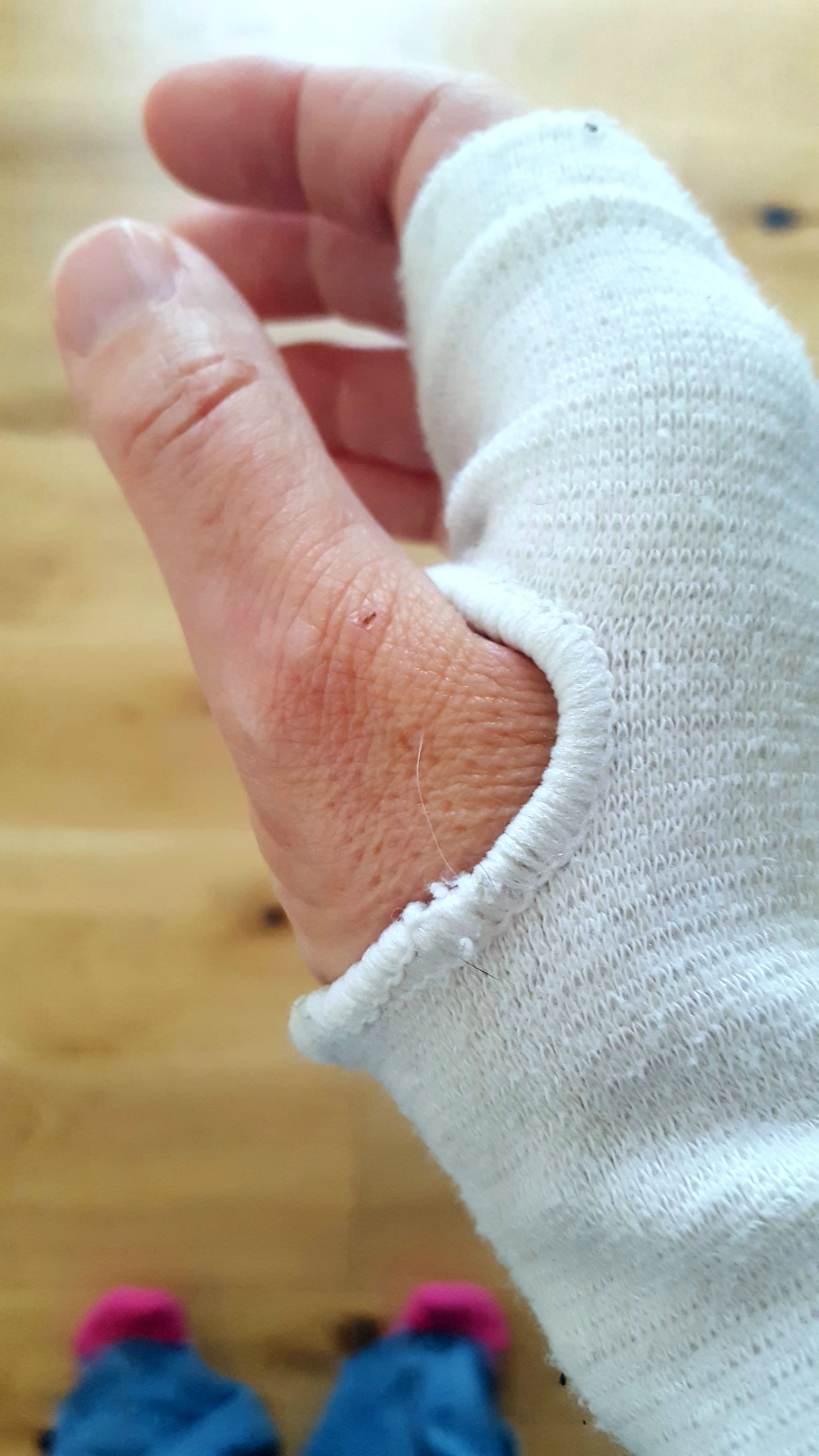 Close up of a hand wearing a wrist support. Socked feet are in the far distance below left.